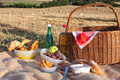 Picnic basket wit food and drinks on field Royalty Free Stock Photo