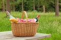 Picnic basket in a woodland setting whicker full of food and drink on table on bright summers day Stock Photos