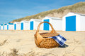 Picnic at beach with blue huts row and white cabins and picmic basket checked napkin Royalty Free Stock Image
