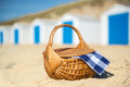 Picnic at beach with blue huts row and white cabins and picmic basket checked napkin Stock Image