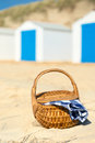 Picnic at beach with blue huts row and white cabins and picmic basket checked napkin Stock Photo