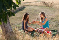 Picnic girls young sharing bread during a in golden evening light Royalty Free Stock Images