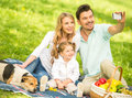 Picnic image of happy young family having outdoors and making selfie Royalty Free Stock Image
