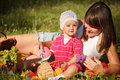 Picnic in the park young beautiful women with her little year old daughter having fun on Stock Photography