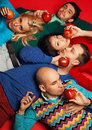 Picnic portrait of five stylish close friends hugging smiling concept holding red apples and lying on red background guys having Royalty Free Stock Image