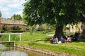 Picnic by the river lower slaughter people sitting under a tree having a along eye in centre of village cotswolds Royalty Free Stock Photography