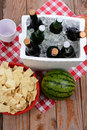 Picnic spread on wood deck high angle shot of a a with red and white checkered table cloth items include beer ice chest cups chips Stock Photos