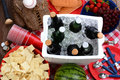 Picnic still life overhead view of a table with ice chest full of beer bowl of chips watermelon strawberries grapes corn chips Stock Photos