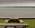 Picnic tables at edge of river two near bank with scenic view Stock Photos
