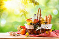 Picnic wicker basket with food on table in the field Royalty Free Stock Photo