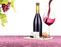 Picnic with wine and food lunch on a red white gingham tablecloth including a bread cheese grapes Royalty Free Stock Photography