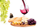 Picnic with wine and food lunch on a wooden board including a bread cheese grapes Royalty Free Stock Photo