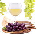 Picnic with wine and food lunch on a wooden board including a bread cheese grapes Royalty Free Stock Photography