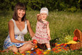 On the picnic young women with her little year old daughter is having in park Royalty Free Stock Photography
