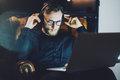 Picture bearded man wearing glasses relaxing modern loft office.Banker sitting vintage chair,listening music laptop Royalty Free Stock Photo