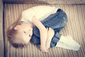 Picture of beautiful child blond girl lying on the sofa hugging knees & looking at camera Royalty Free Stock Photo