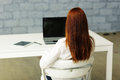 Picture from behind of a businesswoman sitting at her desk Royalty Free Stock Photography