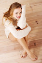 Picture of a careless young caucasian woman on the wooden floor wearing bright sweater Royalty Free Stock Images