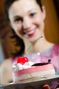 Picture close up on delicious slice of cake with cherry and cream & beautiful young woman brunette girl on the background Royalty Free Stock Photo