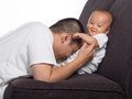 Picture of dad kissing baby tummy and she was laughing and giggling Royalty Free Stock Images