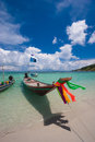 Picture of empty long tail boat on tropical beach. Ko li pe island. Clear water and blue sky with clouds. Vertical Royalty Free Stock Photo