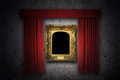 Picture frame in the spotlight vintage gold ornate on a gray wall with red curtains illuminated by Stock Photo