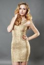 Picture of happy beautiful young woman wearing gold dress posing Royalty Free Stock Photo