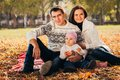 Picture of lovely family in autumn park, young parents with nice adorable kids playing outdoors, five cheerful person have fun on Royalty Free Stock Photo