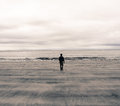 Picture of a man from behind walking on a beach in scotland uk polaroid effect Stock Photos