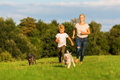 Mother runs with her boy and two small dog on a meadow Royalty Free Stock Photo