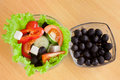 Picture of plates with greek salad and black olives on table Stock Photo