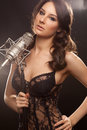 Picture of woman in black with microphone singer studio on Stock Image