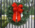 Pine Christmas wreath with pinecones and red bow on a driveway gate, Dallas, Texas Royalty Free Stock Photo