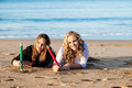 Pictures in the sand two pretty caucasian girls laying on their stomachs drawing with over sized pencils happily Stock Photo