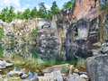 Picturesque lake in the ancient stone quarry sweden surrounded by rocks and trees abandoned many years ago Royalty Free Stock Photos