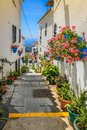 Picturesque street of Mijas with flower pots in facades. Andalus Royalty Free Stock Photo