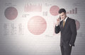 Pie charts and numbers on wall with salesman young sales business male in elegant suit standing in front of brick background lines Royalty Free Stock Photos