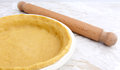 Pie dish lined with pastry with a rolling pin Royalty Free Stock Photo