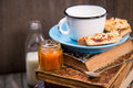 Pie with milk some pieces of apricot jam and on old book Royalty Free Stock Photography