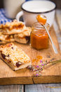 Pie with milk some pieces of apricot jam and on wooden plate Royalty Free Stock Image