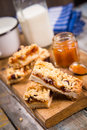 Pie with milk some pieces of apricot jam and on wooden plate Stock Photos