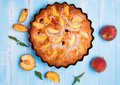 Pie with peaches and raspberry delicious on the blue background up view Stock Image