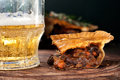 Piece of australian meat pie with a glass light beer on the table rustic style Royalty Free Stock Image
