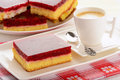 Piece of biscuit cake with cream and cherry jelly and cup of coffee. Royalty Free Stock Photo
