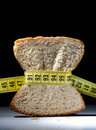 Piece of bread grasped by measuring tape Stock Photos