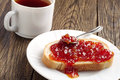 Piece of bread with jam and tea cup on old wooden table Stock Photo