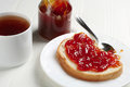 Piece of bread with jam and tea cup on white table Stock Images