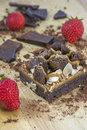 Piece of brownie with chocolate and several strawberries on the wooden background Royalty Free Stock Photo
