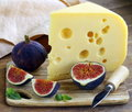 Piece of cheese maasdam with fresh figs on a wooden board Stock Images