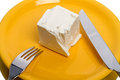 Piece of cheese on plate a yellow close up Stock Image